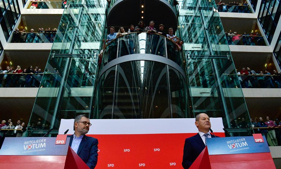 Tesoureiro dp SPD, Dietmar Nietan (à esquerda) e outros integrantes do partido observam pronunciamento do líder interino Olaf Scholz sobre os resultados do referendo