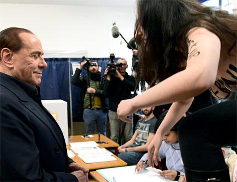 """Ativista - supostamente do grupo Femen - salta em mesa na frente de Silvio Berlusconi, líder do partido de direita Forza Italia, para protestar de topless com a frase """"Berlusconi, você expirou"""" pintada sobre os seios."""