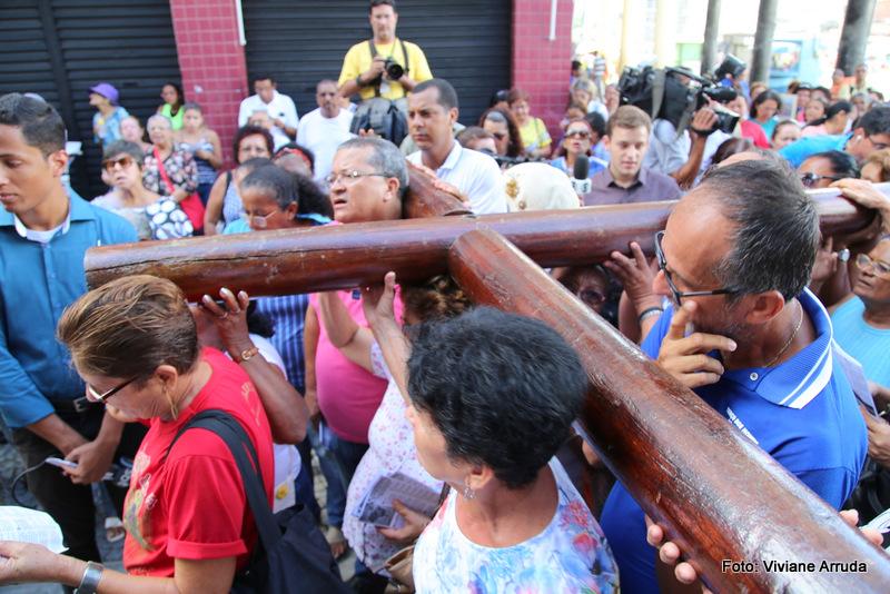 Cristãos carregam cruz durante caminhada