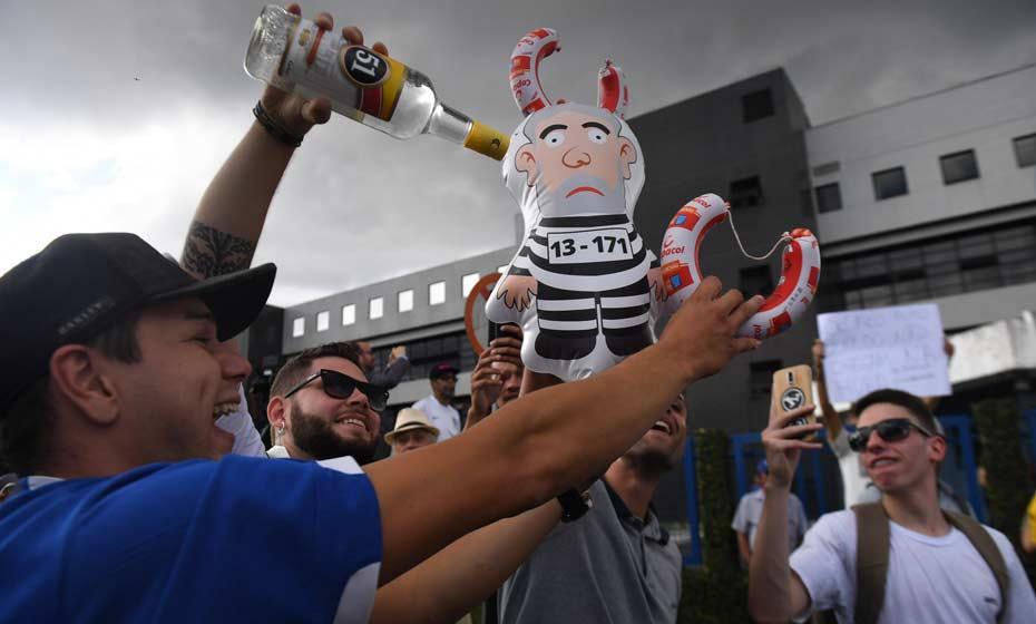 """Em Curitiba, manifestante representa boneco de Lula preso junto com garrafa da cachaça 51, cujo slogan era """"Uma boa ideia"""""""