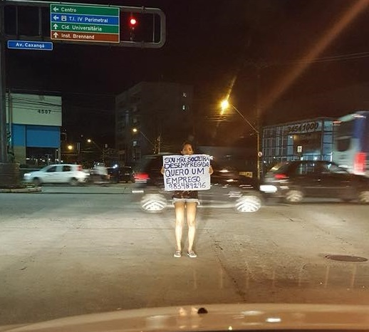 Segurando cartolina, mulher pede emprego na avenida Caxangá, no Recife
