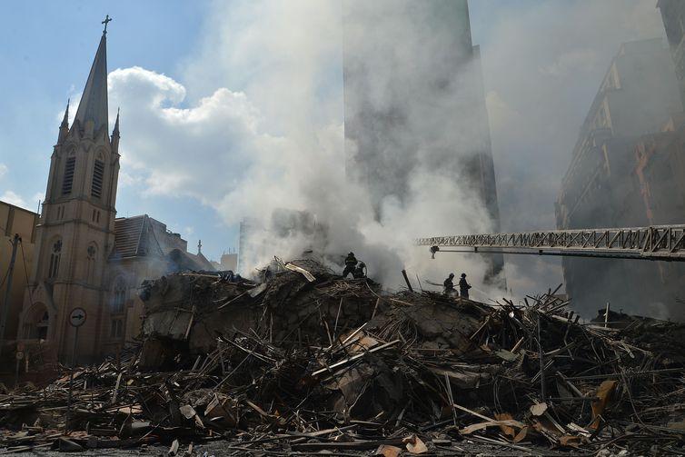 Bombeiros em meio aos destroços do prédio que desabou
