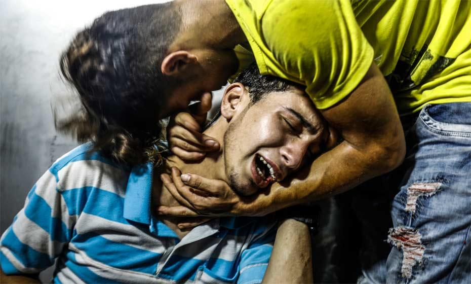 Jovens palestinos choram no necrotério do hospital após morte de dois adolescentes em série de ataques