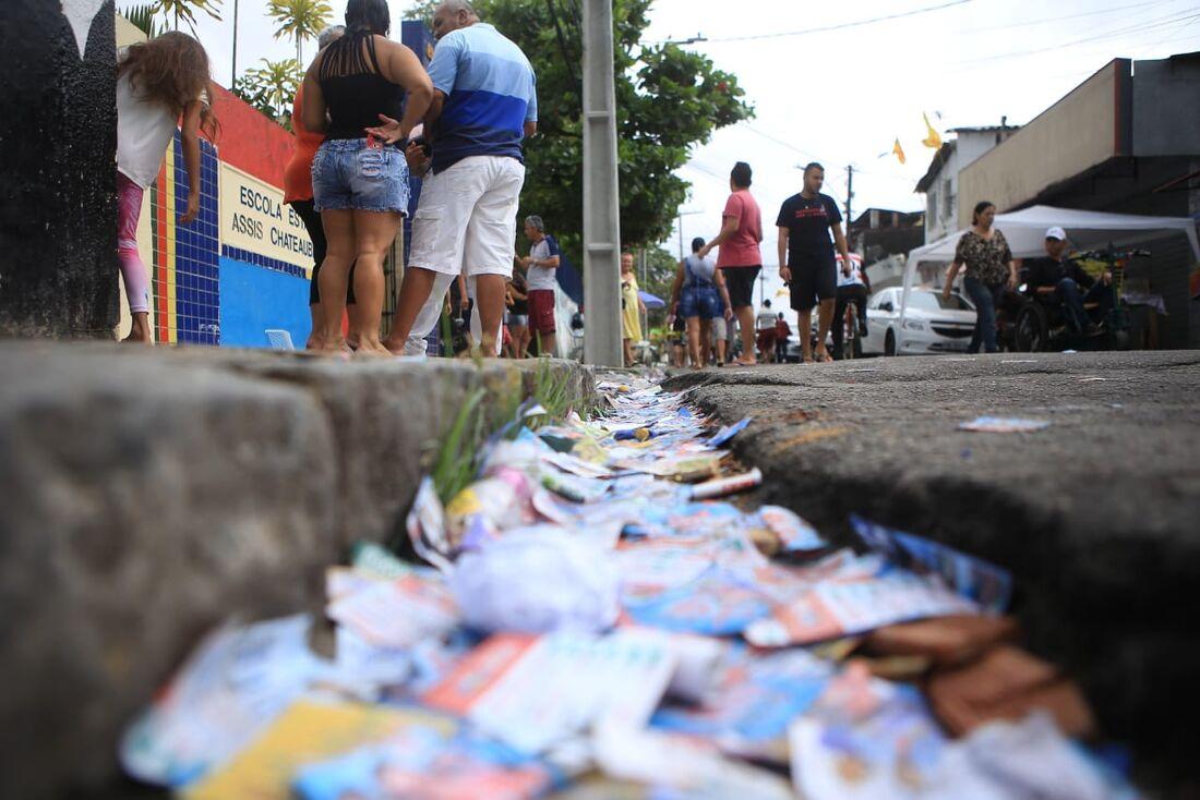 Muitos santinhos espalhados no chão em frente à Escola Assis Chateaubriand, em Brasília Teimosa