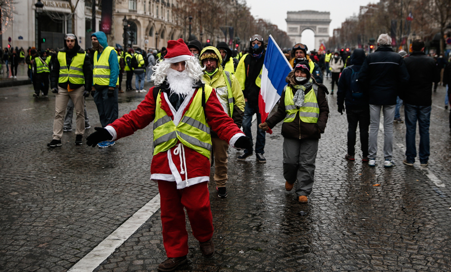Manifestante 'colete amarelo' se veste de Papai Noel durante protesto na Champs Elyseés
