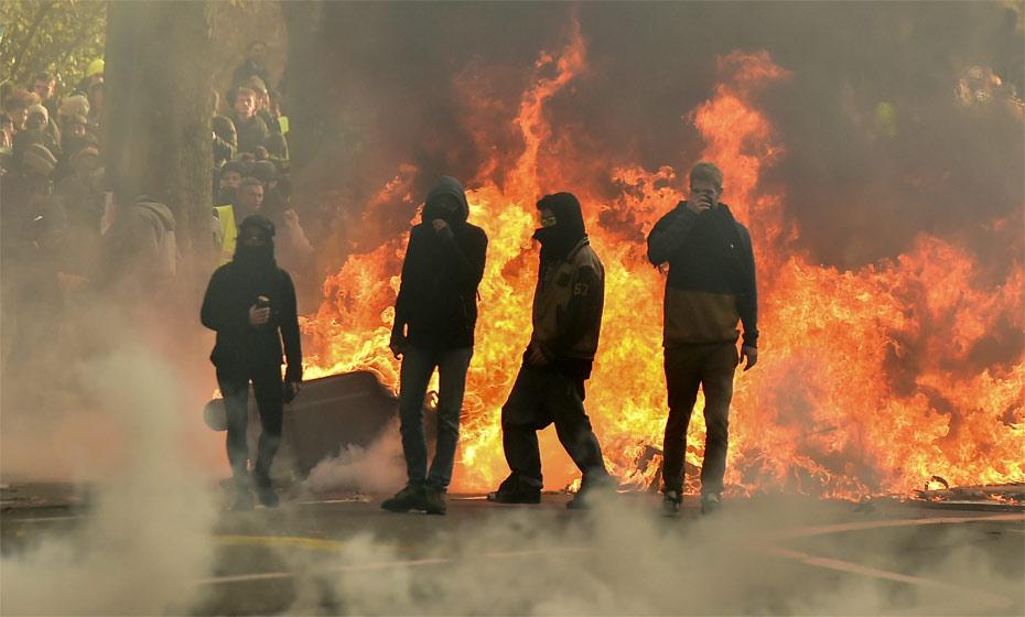 Manifestantes em frente a barricada em chamas no protesto dos coletes amarelos em Tolouse