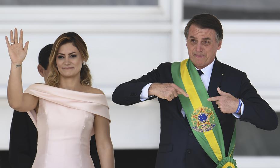 Michelle Bolsonaro acena e Bolsonaro mostra faixa