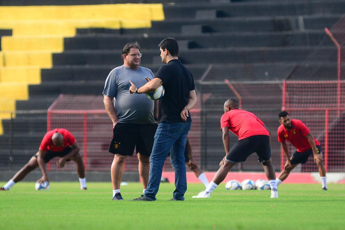Treinador Guto Ferreira conversa com Lucas Drubsky no centro do gramado.