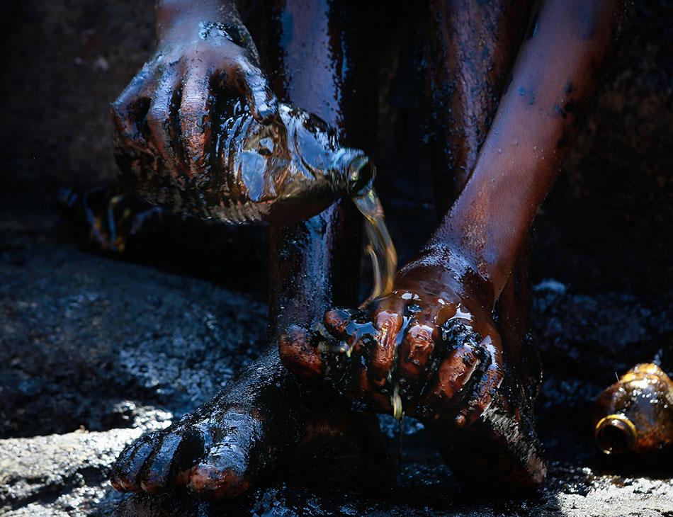 Criança tenta se livrar do óleo preso ao corpo após ajudar na limpeza na praia de Itapuama, Cabo de Santo Agostinho, Região Metropolitana do Recife