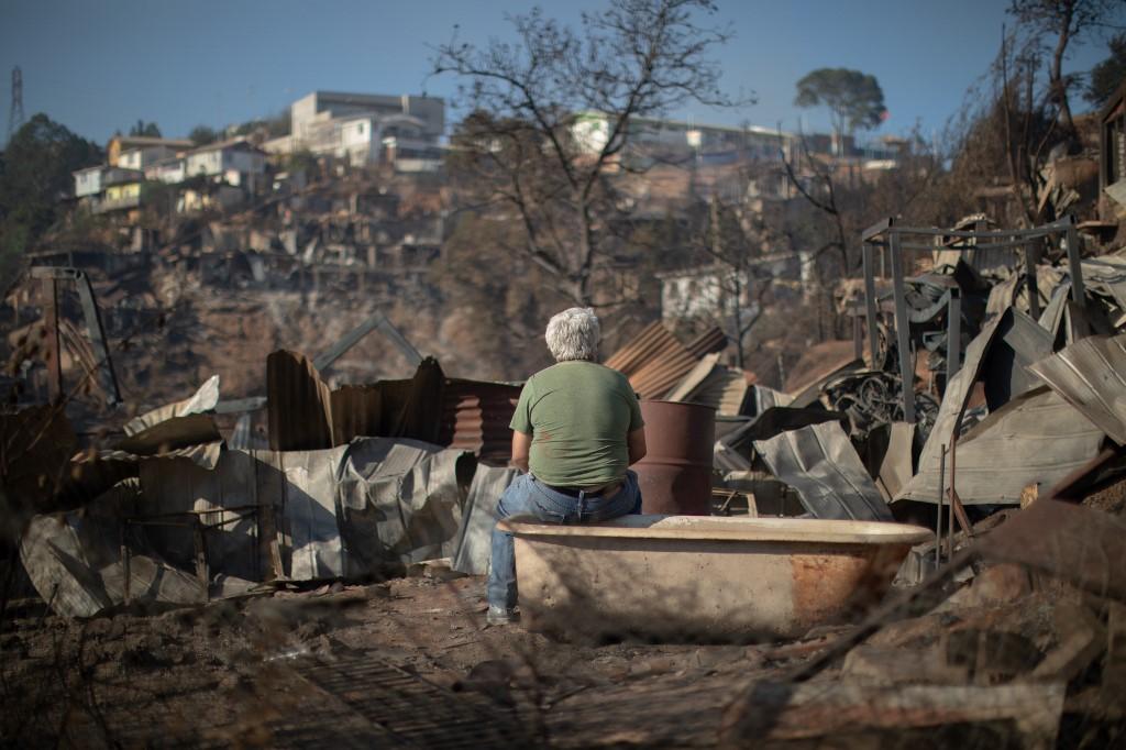 Homem observa a destruição causada pelo incêndio em Valparaíso