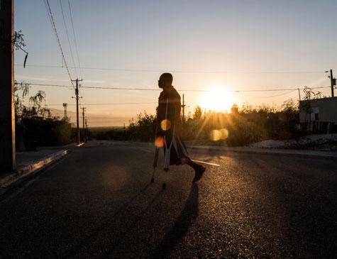 Boulva Verly, de 42 anos, caminha com muletas após perder perna no terremoto ocorrido em 2010 no Haiti