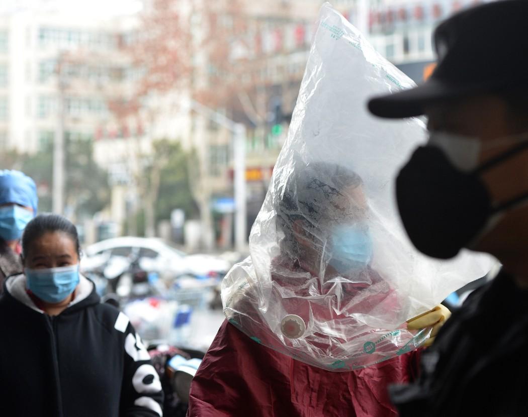 Pedestre se protege com máscara e sacola plástica nas ruas de Wuhan