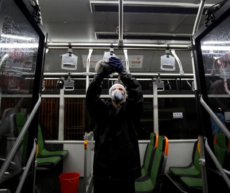 Trabalhador realiza limpeza de ônibus em Teerã, capital do Irã