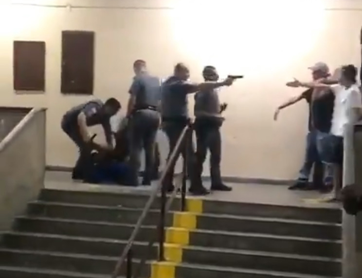 PMs agredindo e apontando uma arma de fogo a estudantes em escola de São Paulo