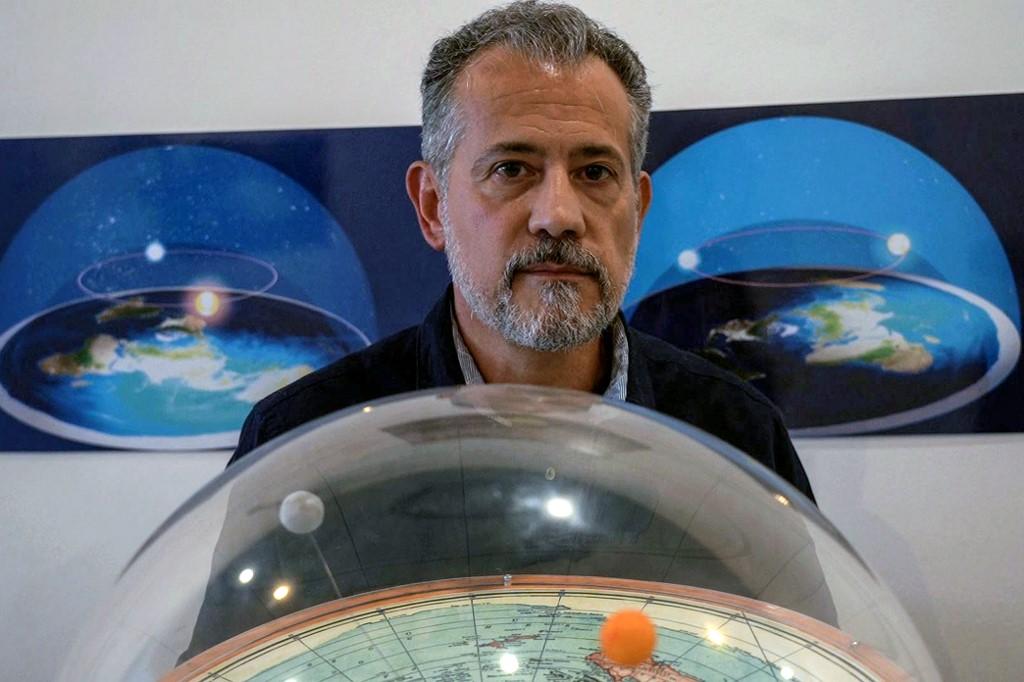 O teórico brasileiro da conspiração da terra plana, Anderson Neves, mantém um modelo de terra plana cercado por uma cúpula durante uma entrevista à AFP em São Paulo