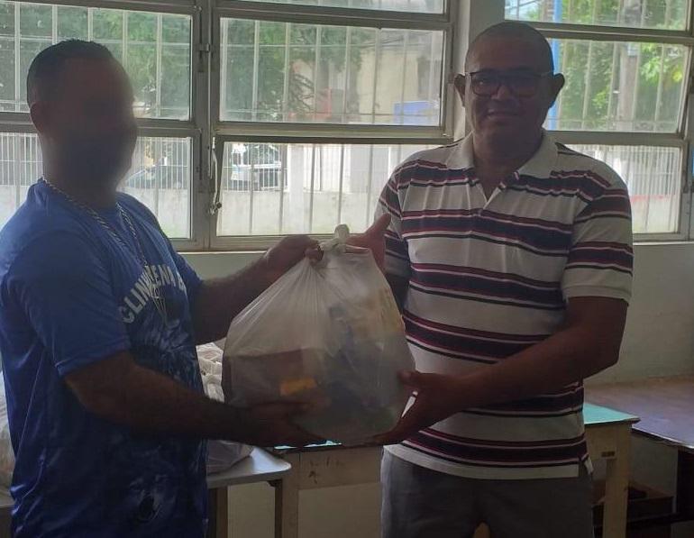 J.A.F (de camisa azul) monta os kits de produtos doados pela prefeitura e realiza a distribuição para os 938 alunos da instituição