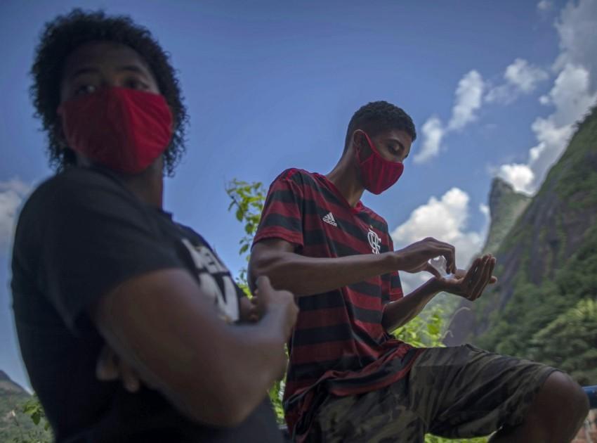 Meninos higienizam as mãos em rua do Rio de Janeiro