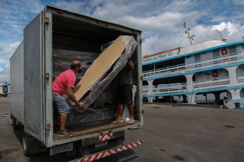 Homem retira caixões do caminhão, no Amazonas