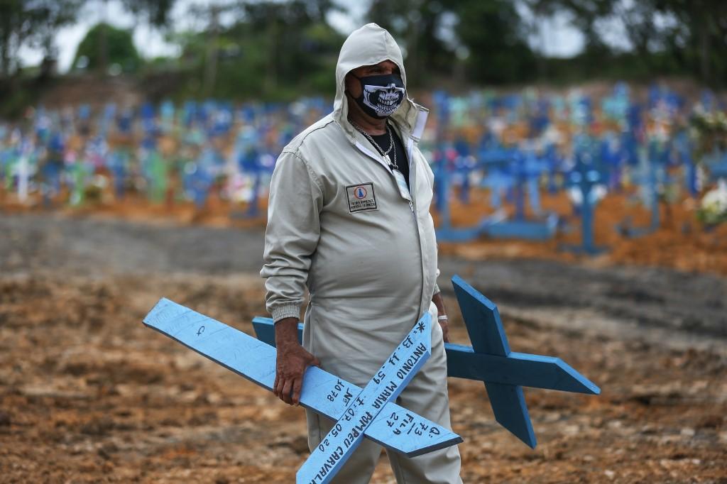 Trabalhador prepara cruzes em cemitério de Manaus, AM