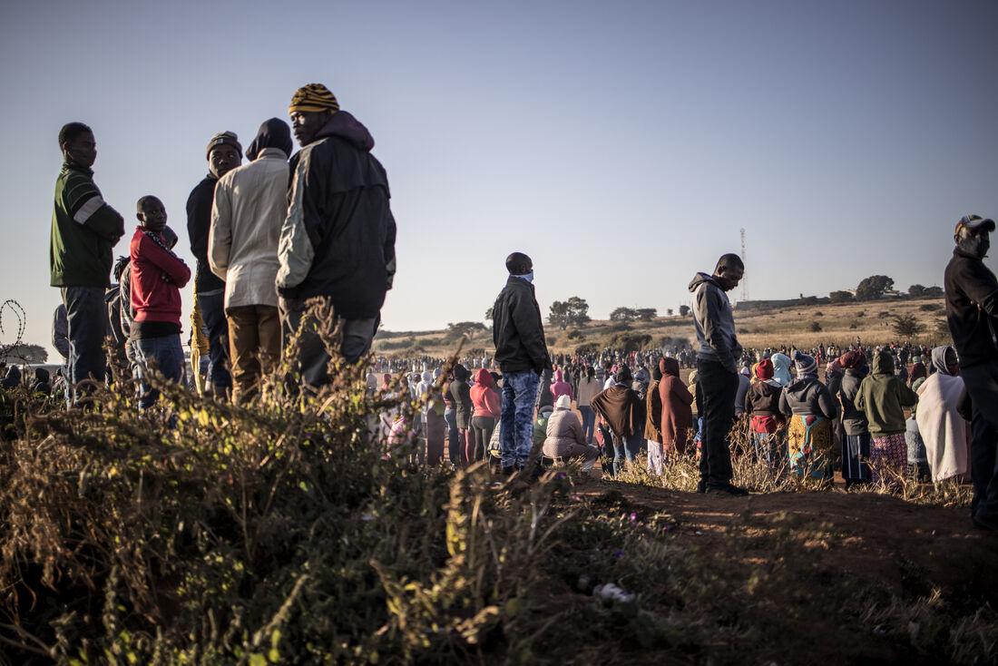Residentes da África do Sul se organizam em fila para receber insumos de prevenção a Covid-19.