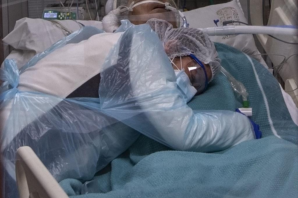 Pessoa com vestes de proteção abraça paciente diagnosticado com Covid-19 em hospital de Santiago, no Chile