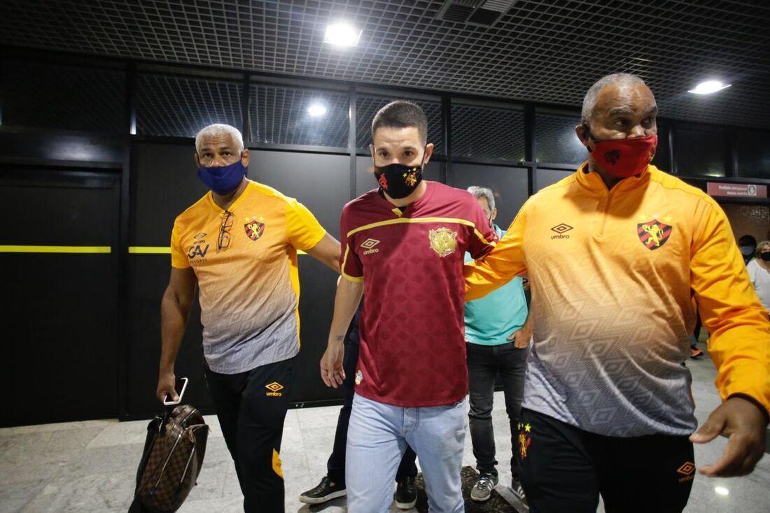 Thiago Neves é acompanhado por seguranças em desembarque no Recife