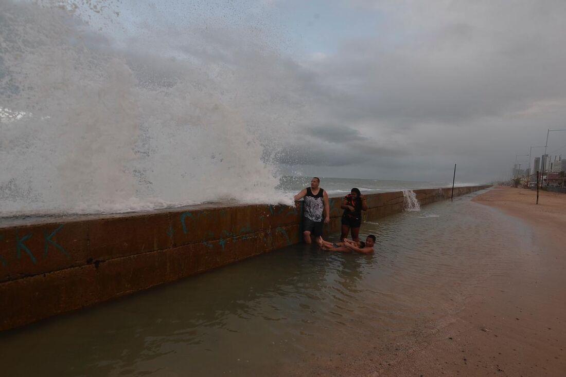 Passantes observam a ressaca do mar na praia de Boa Viagem