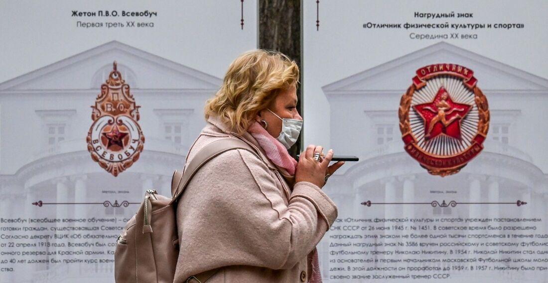 Mulher usando máscara ao andar nas ruas de Moscow