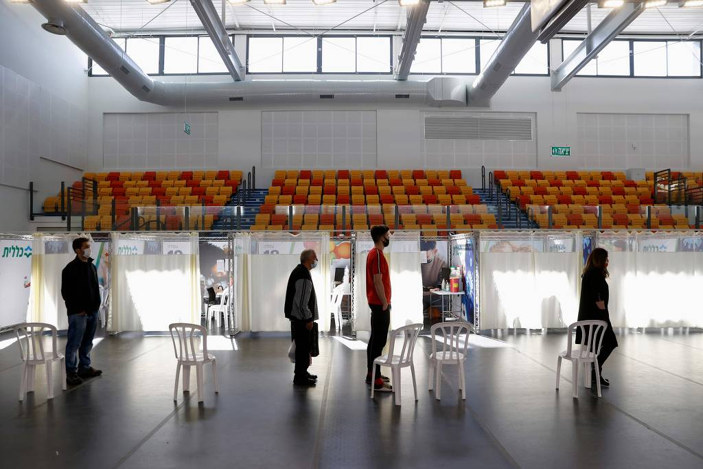 Israelenses em um ginásio na cidade de Petah Tikva para receber a vacina