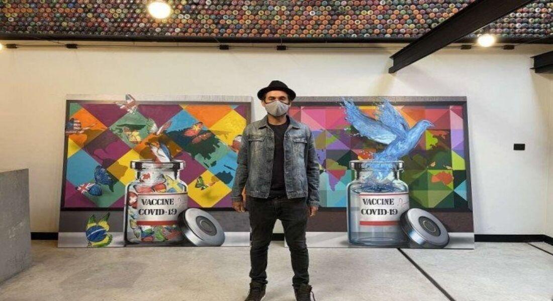 Eduardo Kobra ao lado de painéis