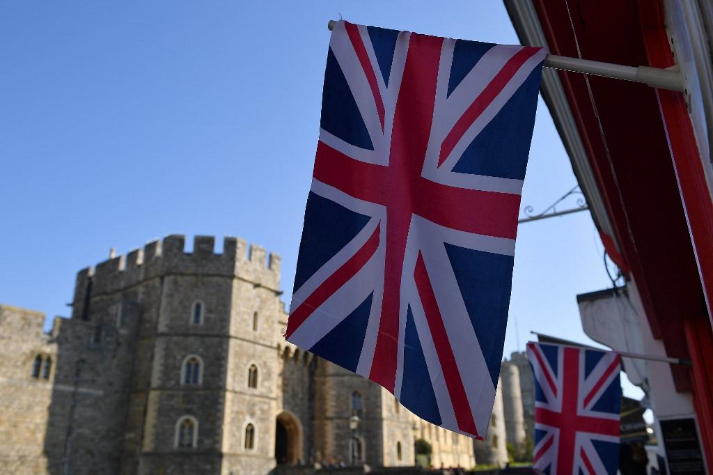 Uma bandeira da União voa acima da vitrine de uma loja em frente ao Castelo de Windsor