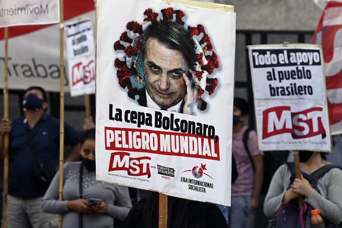 Pessoas seguram faixas representando o presidente do Brasil Jair Bolsonaro durante um protesto em frente à Embaixada do Brasil em Buenos Aires, no dia 14 de abril