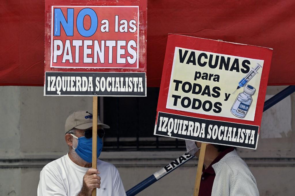 """Pessoas seguram faixas com os dizeres """"Vacinas para todos"""" e """"Não às patentes"""" durante um protesto"""