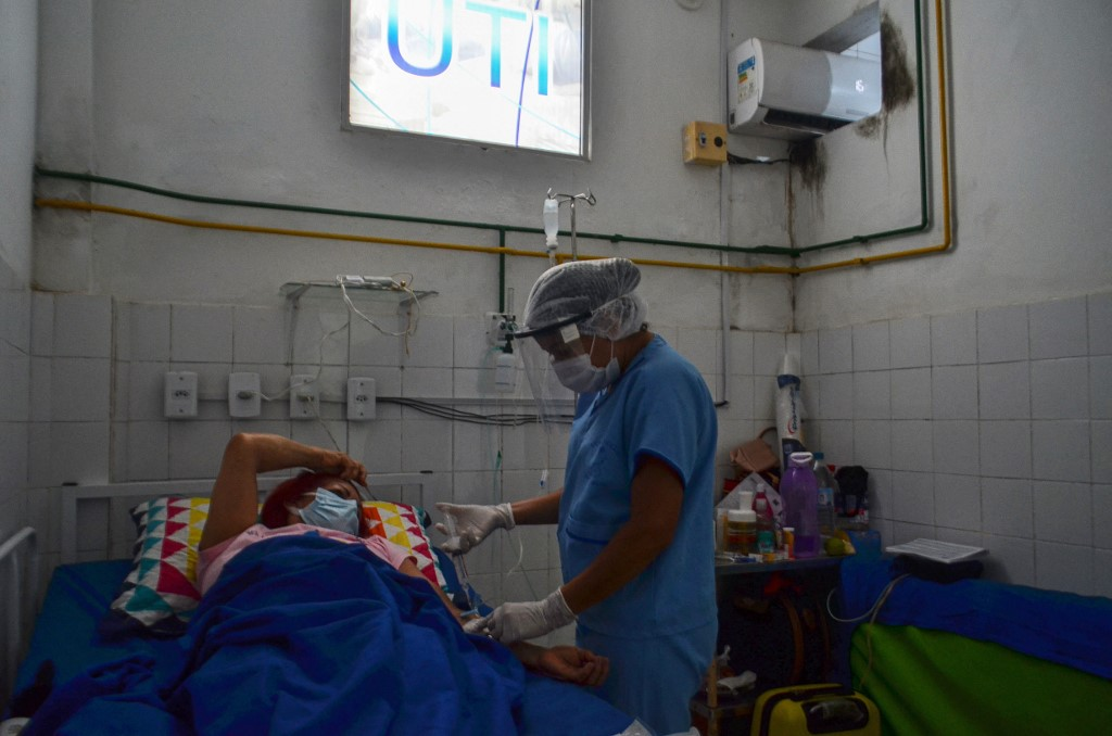 Um trabalhador de saúde atende um paciente Covid-19 dentro de uma UTI em Hospital Público