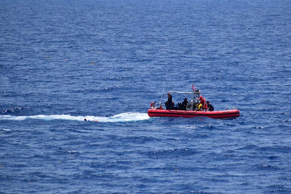 Pequeno barco da Guarda Costeira tenta resgatar pessoas da água a aproximadamente 18 milhas a sudoeste de Key West, Flórida