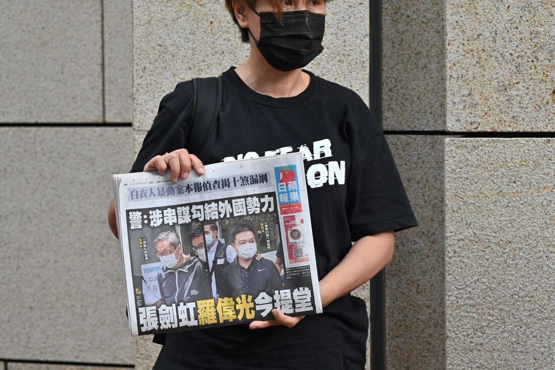 Um apoiador de do executivos do jornal pró-democracia Apple Daily de Hong Kong, o editor-chefe Ryan Law e o CEO Cheung Kim-hung, segurando um exemplar do jornal durante um protesto fora do tribunal em Hong Kong em 19 de junho de 2021, após os dois serem a