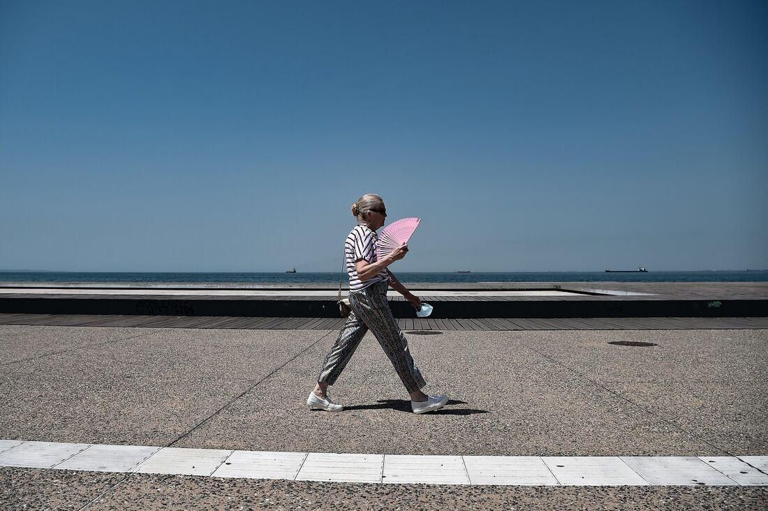 Mulher caminha sem mpascara na orla de Thessalonuk, Grécia