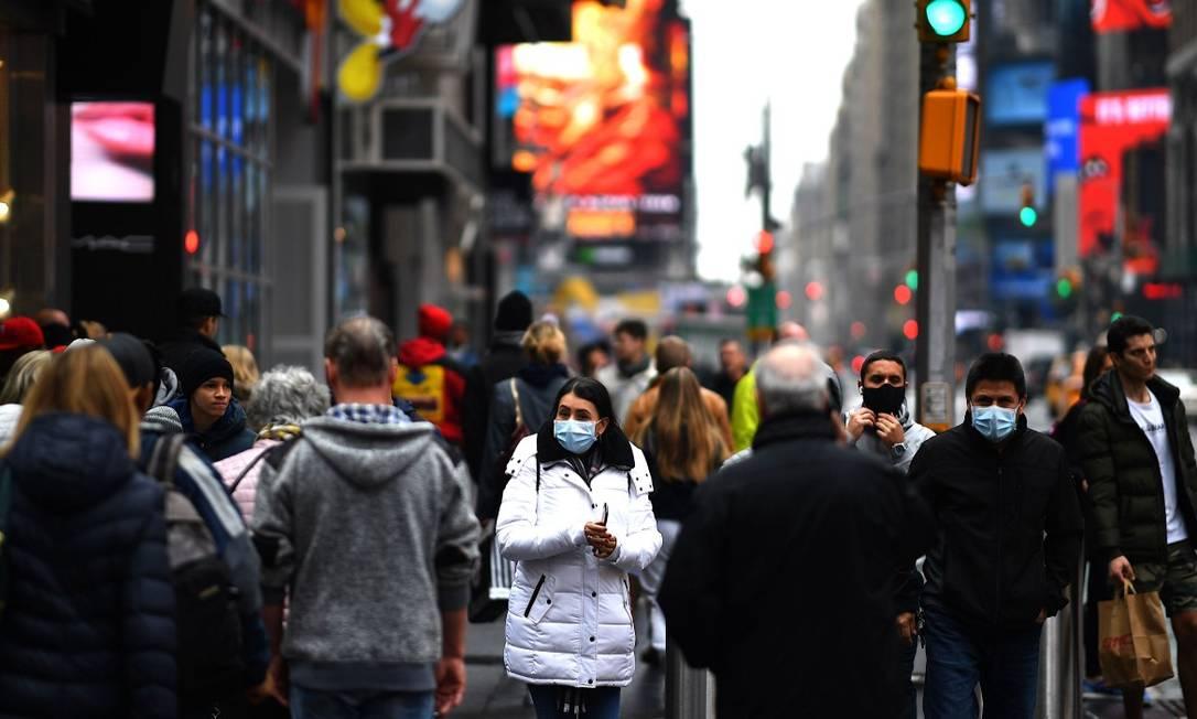 Pessoas caminham com máscaras de proteção em Times Square