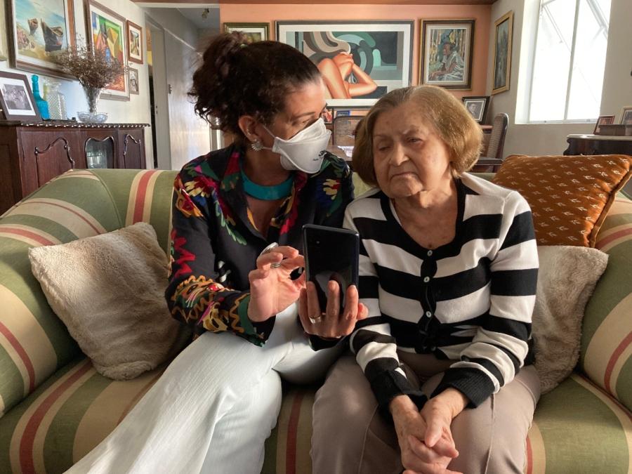 Pelo celular, com ajuda de Laís, Aurélia Godoy, 90, se comunica com a outra filha, que mora na Itália